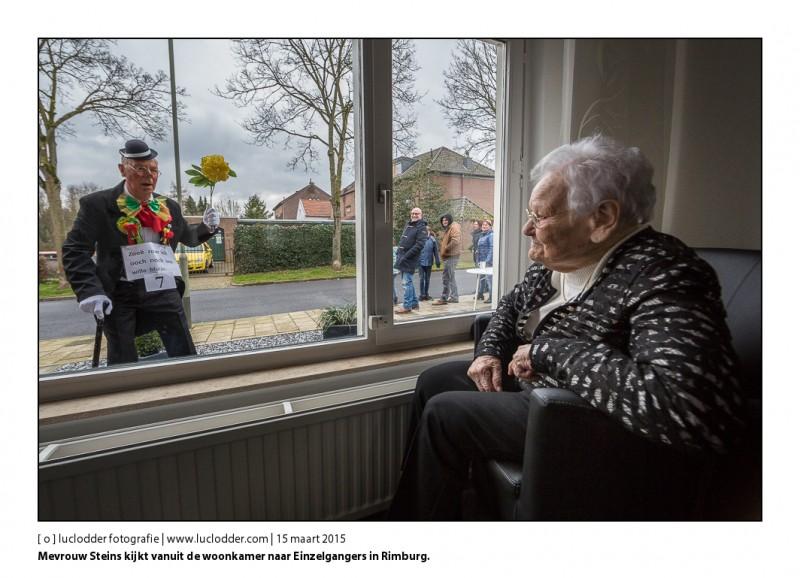 Mevrouw Steins kijkt vanuit het woonkamer raam van haar kleindochter en ziet de ene na de andere Einzelganger voorbijgaan. Einzelgangersoptocht in Rimburg