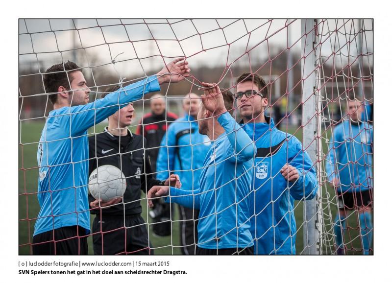 SVN Spelers en staf laten zien aan scheidsrechter Dragstra waar de bal door het net moet zijn gegaan. Een kopbal die door het net ging werd door hem afgekeurd. RKHBS-SVN (amateurvoetbal, 3A)